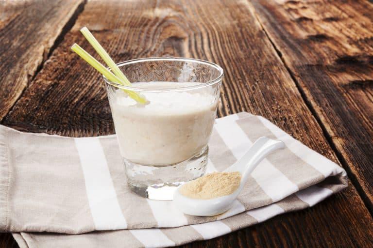 Löffel mit Maca Pulver vor Milchglas