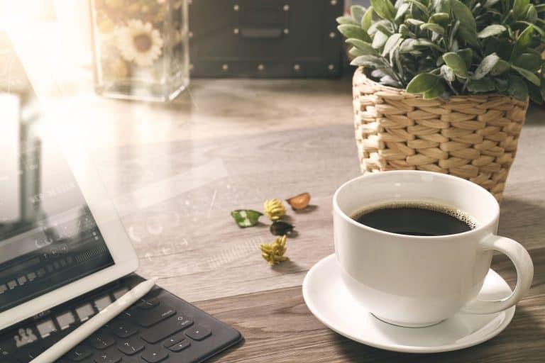 Tasse Kaffee neben PC