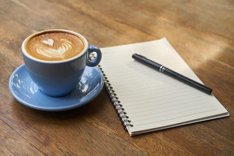 Tasse Kaffee neben Schreibblock