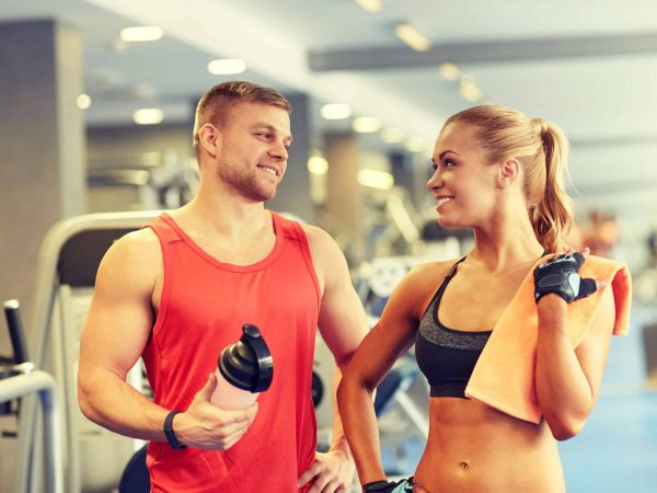 sport, fitness, lifestyle and people concept – smiling man and woman with protein shake bottle and towel talking in gym