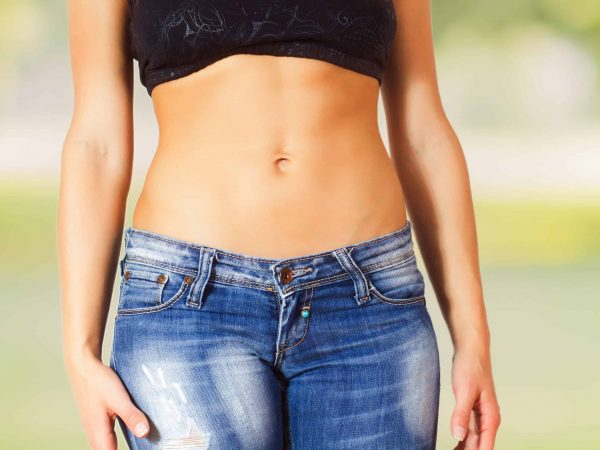 Slim Female with perfect healthy fit body, showing her thin waist.  Caucasian young woman in jeans. Unrecognizable person.Diet and weight loss concept.