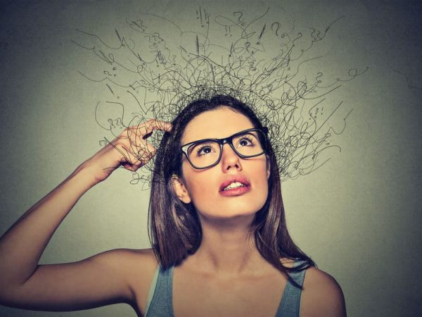 51742512 – closeup portrait young woman scratching head, thinking daydreaming with brain melting into lines question marks looking up isolated on gray background. human facial expressions, emotion feeling sign