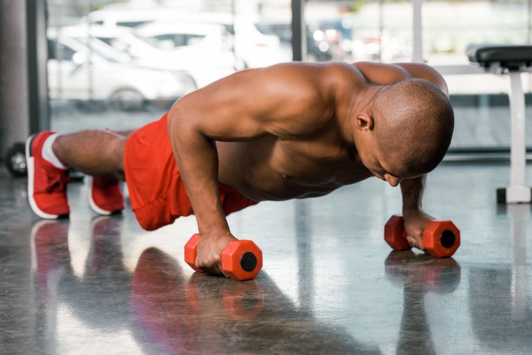 shirtless muscular african american sportsman doing push ups with dumbbells at gym