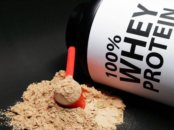 Whey Protein Powder in measuring scoop. Bodybuilding Nutrition Supplements.
