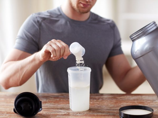 sport, fitness, healthy lifestyle and people concept – close up of man with jar and bottle preparing protein shake