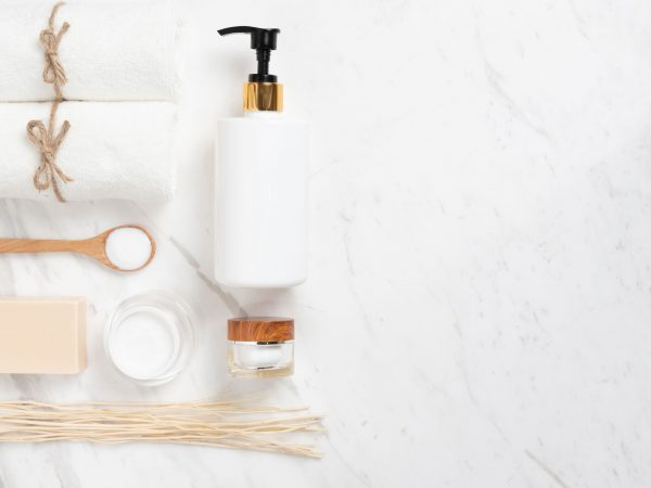 Top view of Cosmetic bottles, soap, wooden spoon and towel on white marble background. Spa products with copy space.