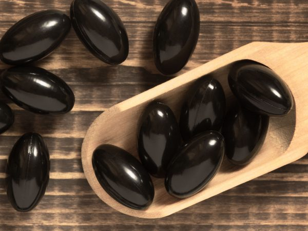 Astaxanthin supplement soft gel capsules. Black pills in a spoon on wood background. Natural red algae antioxidant. Closeup, top view