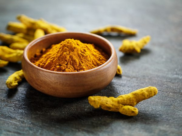Turmeric in a bowl and curcuma root. Selective focus.