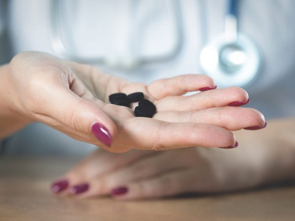 Doctor showing in hands activated charcoal.