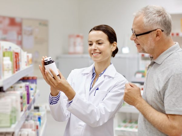 medicine, pharmaceutics, health care and people concept – happy pharmacist showing drug to senior man customer at drugstore