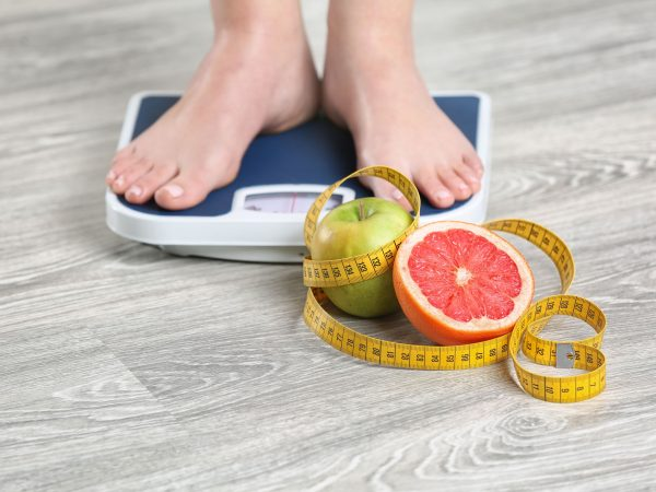 Woman standing on scales near fruits and measuring tape on wooden floor. Concept of weight loss